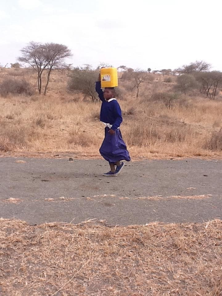 tanzanian pupil with bucket of water